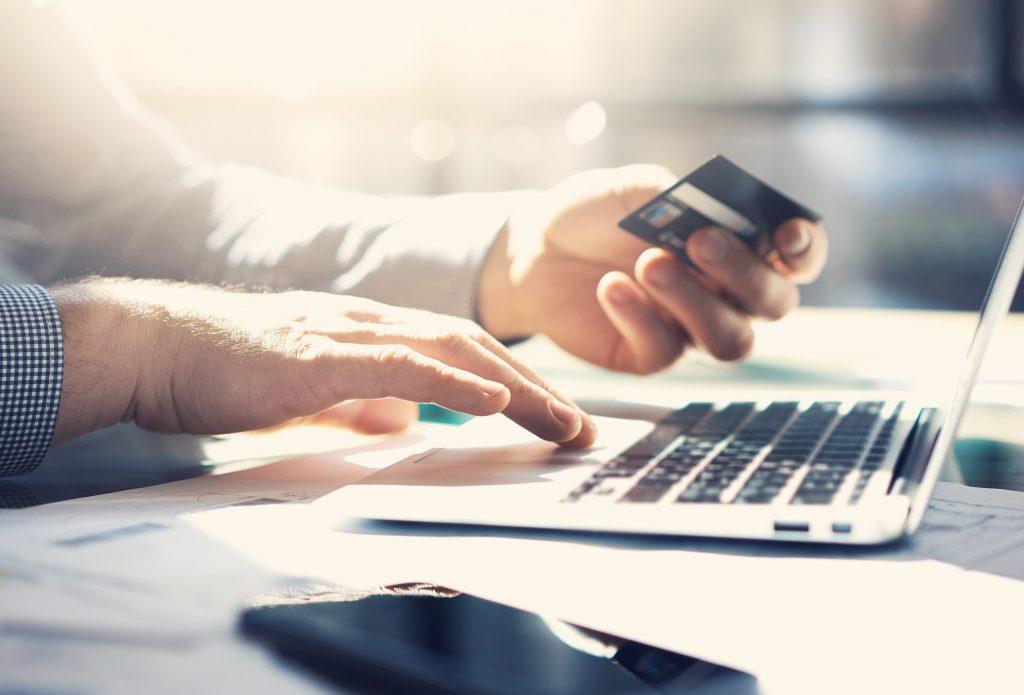 Man Holding Credit Card at Laptop