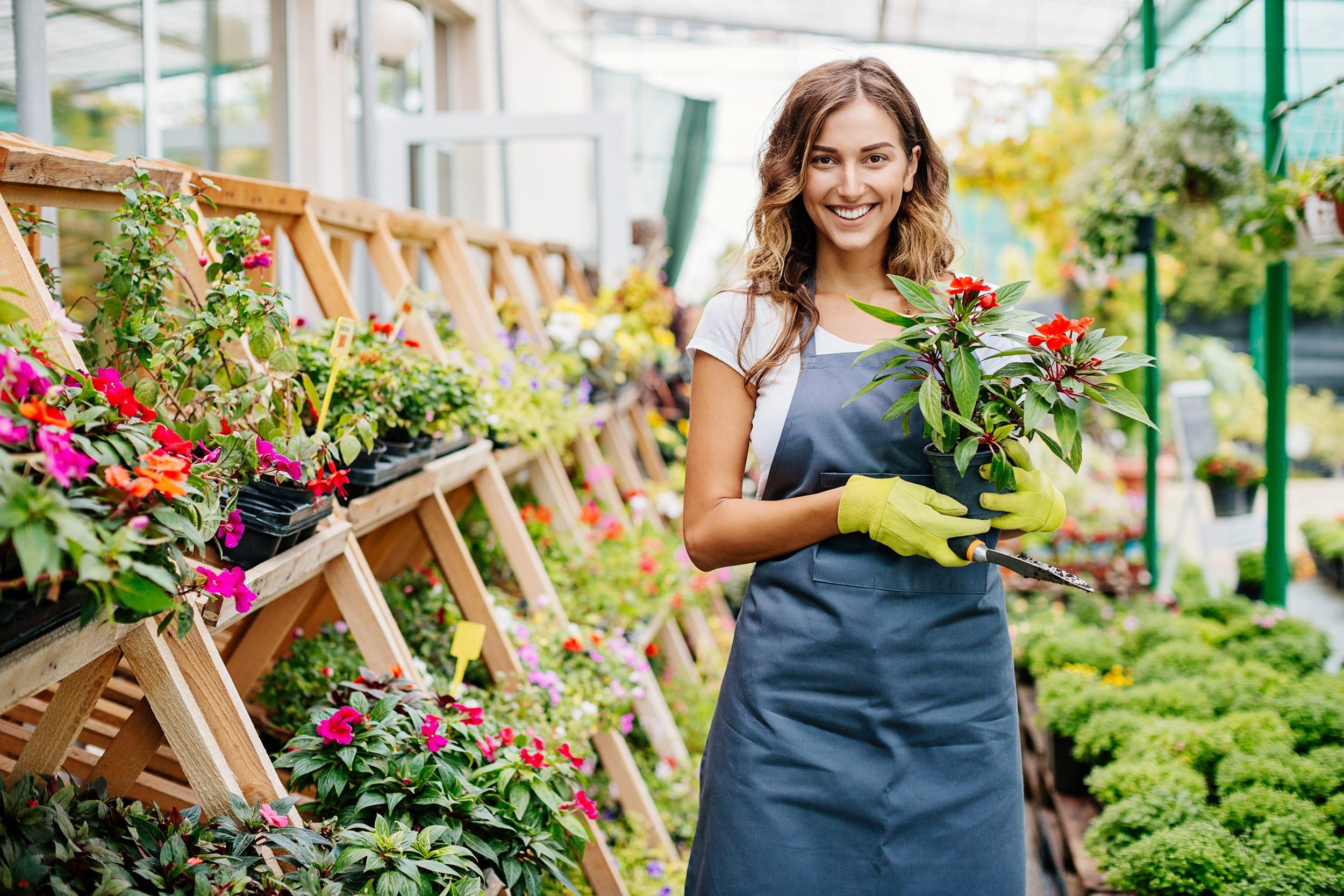 Woman Holding Flowers in Nursery