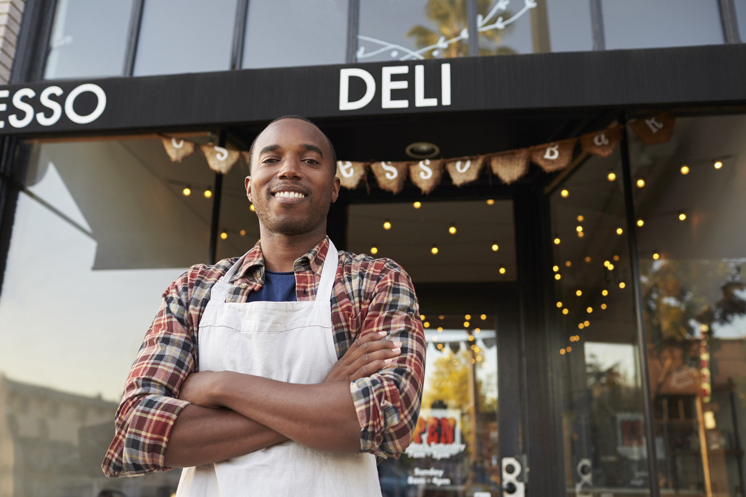 Man Standing in Front of Deli