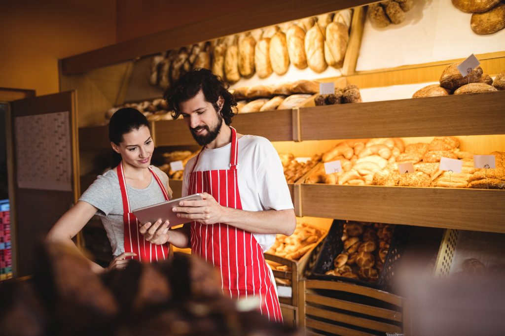 Couple Checking Tablet at Bakery